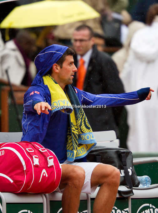 30-05-13, Tennis, France, Paris, Roland Garros,  Novak Djokovic puts on his rain jacket