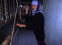 Afghan Women weaving a cover fabric