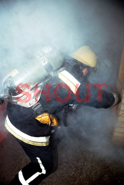 Firefighters, in breathing apparatus, are preparing to enter the front door of a house on fire. This image may only be used to portray the subject in a positive manner..©shoutpictures.com..john@shoutpictures.com