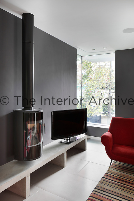 An informal living room with grey walls and a tiled floor. A cyclindrical wood burning stove is suspended upon the wall. A television is placed on a simple concrete shelf.