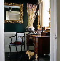 A formal desk and armchair at one end of the hallway creates an impromptu study
