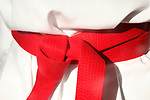Close up of red belt karate costume tied around stomach