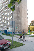Mom wheeling baby to Bloc housing a reminder of the Communist era. Balucki District Lodz Central Poland