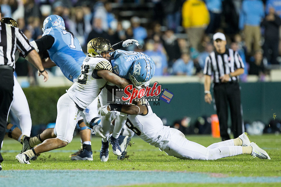Marquise Williams (12) of the North Carolina Tar Heels is tackled by Brandon Chubb (48) and Marquel Lee (8) of the Wake Forest Demon Deacons during first half action at Keenan Stadium on October 17, 2015 in Chapel Hill, North Carolina.   (Brian Westerholt/Sports On Film)