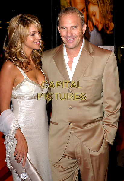 CHRISTINE BAUMGARTNER & KEVIN COSTNER.Attends New Line Cinema's World Premiere of Upside of Anger held at the Mann National Theatre in Westwood, California  .March 3rd 2005.half length married couple husband wife beige brown silk satin suit white dress hand in pocket.www.capitalpictures.com.sales@capitalpictures.com.Supplied By Capital PIctures