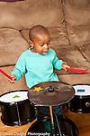 Two year old toddler boy playing musical instrument drum set