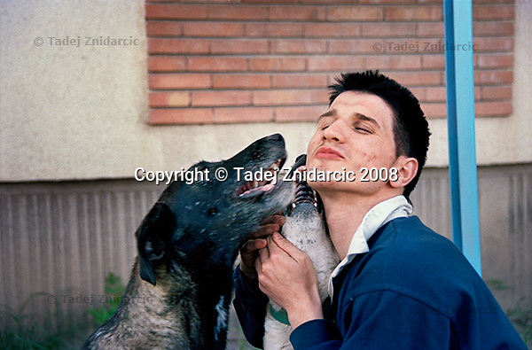 Catalin plays with stray dogs. Iasi, Romania.