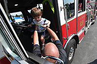 NWA Democrat-Gazette/J.T. WAMPLER Asher Shamblin, 4, gets a boost from Bella Vista fire captain Brandon Earley while checking out a ladder truck Sunday Sept 8, 2019 at the Bella Vista Farmers Market. The city's first responders were on hand to show some of the equipment that they use in their day-to-day operations. Free child fingerprinting was also available.<br />The Bella Vista Farmers Market operates every Sunday through October 13 from 9 a.m. to 2 p.m. in the parking lot of Sugar Creek Center. Fresh produce and locally handmade goods are available. For more information or to stay up to date of current vendors and programs, follow the market on Facebook at Bella Vista Farmers Market.