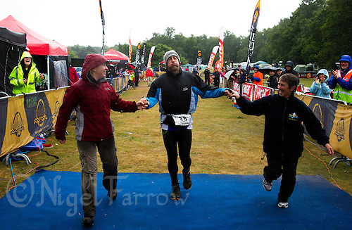 12 JUN 2011 - BRANSGORE, GBR - Chris Ette (centre) crosses the finish line to win the Triple Enduroman at the Enduroman Ultra Triathlon Championships, accompanied by his wife Sam Ette (left) and his mother Lynne Ette (right) (PHOTO (C) NIGEL FARROW)