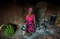 Uganda, Mukono. Prossy Nanyonga at home with the BioLite home cook stove that produces light and charges mobile phones.
