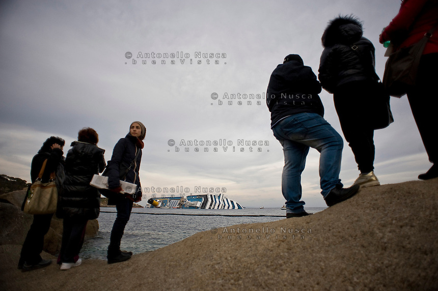 Isola del Giglio, Italy, January 19, 2012. People look at the Costa Concordia aground in front of the harbour of the Isola del Giglio (Giglio island) after hitting underwater rocks.