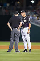 Charlotte Knights manager Joel Skinner (37) discusses a call at second base with umpire Nick Lentz during the game against the Scranton/Wilkes-Barre RailRiders at BB&T Ballpark on July 17, 2014 in Charlotte, North Carolina.  The Knights defeated the RailRiders 9-5.  (Brian Westerholt/Four Seam Images)