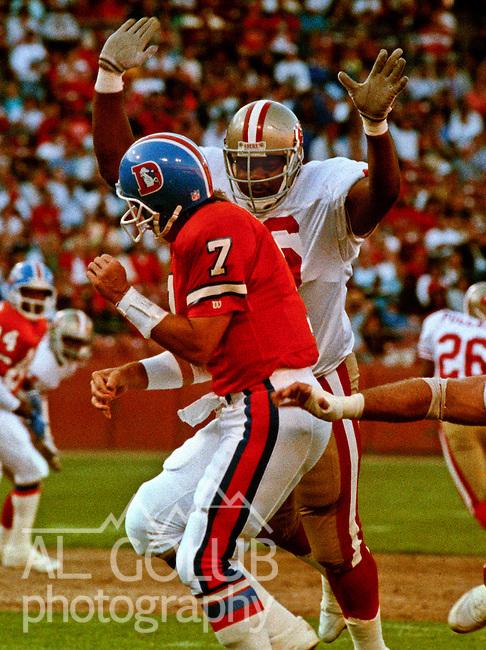 San Francisco 49ers vs. Denver Broncos at Candlestick Park Wednesday, August 7, 1991.  49ers beat Broncos 24-6 in preseason game.  49er defensive end Dennis Brown (96) lands on Broncos quarter back John Elway (7).