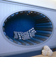 Detail of an oval niche bed in a blue clapboard wall