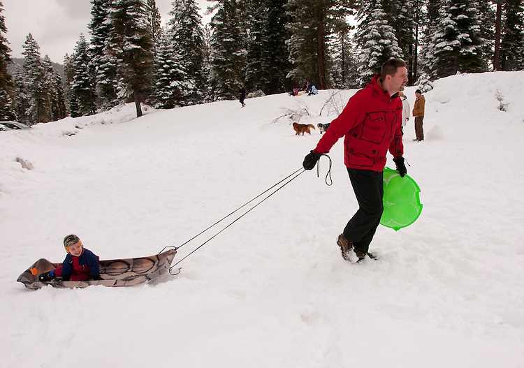 California, Lake Tahoe: Child and father enjoy snow play with sled at North Lake Tahoe Regional Park.  Photo copyright Lee Foster.  Photo # cataho107498
