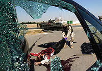 A soldier drags an insurgents body from the street. A counter sniper team killed the three men who fired at an Iraqi checkpoint from their car. Mosul, Iraq. Friday July 8, 2005.