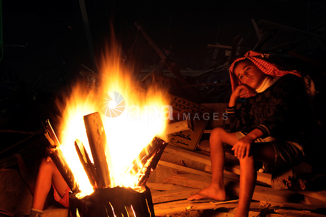 A Palestinian boy warms himself by a fire outside their tent after Israeli forces destroyed their family house in the East Jerusalem neighbourhood of Beit Hanina, which falls in the West Bank side of Israel's separation barrier on Nov. 02, 2013. According to Israeli Authorities the house was built without a permit. Photo by Saeed Qaq