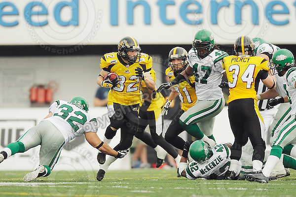 July 12, 2008; Hamilton, ON, CAN; Hamilton Tiger-Cats running back Tre Smith (32) is tackled by Saskatchewan Roughriders fullback Neal Hughes (32) during the CFL football game at Ivor Wynne Stadium. The Roughriders defeated the Tiger-Cats 33-28. Mandatory Credit: Ron Scheffler.