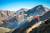 Trail running in the wide open brown landscape of the Albula Pass, in autumn, Switzerland.
