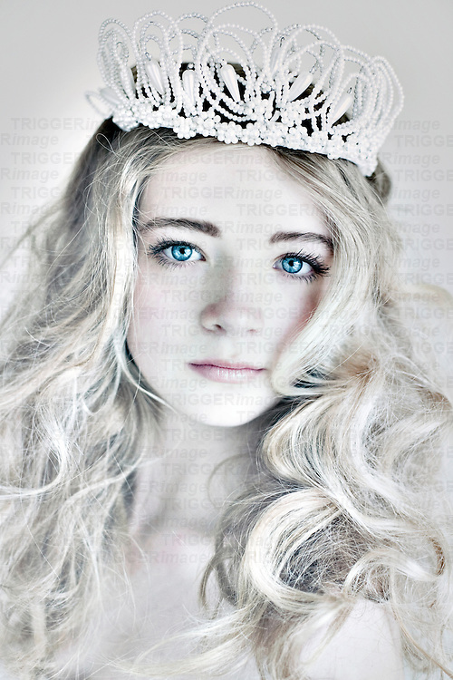 Female youth with fresh skin and clear blue eyes and blonde hair wearing crown