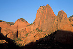Golden sunset light on red sandstone peaks and sheer rock cliffs in the Kolob Canyon area, Zion National Park, Utah
