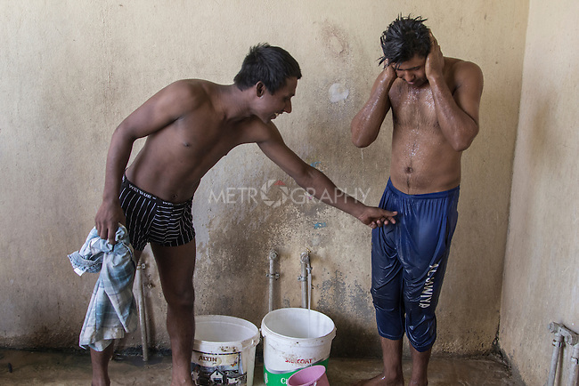 10/10/2014 -- Kirkuk, Iraq -- Two Bangladeshi workers joke with each other in the bathroom of the garage where they live on Kornish street.