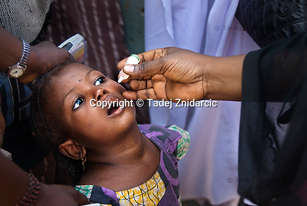 A girl receives polio vaccine in Kaduna, northern Nigeria city, during polio national immunization days (NIDs). NIDs are held four times a year and teams of vaccinators try to reach every child in Nigeria.