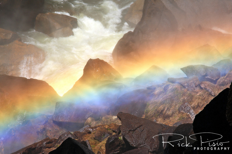 A rainbow forms in the mist along the Mist Trail near Vernal Falls in Yosemite National Park