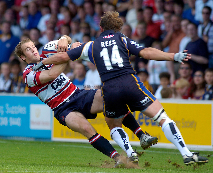 Photo. Glyn Thomas. .Leeds Tykes v Gloucester. .Zurich Premiership. 05/09/2004..Gloucester's James Simpson-Daniel (L) is knocked down by David Rees.