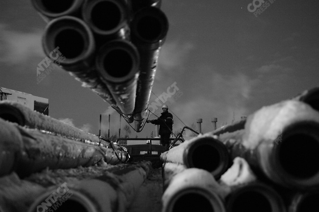 At a site in the vast Nefteyugansk oilfield in Siberia, Russia, the Siberian Geophysical Company, part of the oil services giant Schlumberger, are preparing wells for Rosneft, here a truck bringing new pipe for drilling was unloaded by workers. Siberia, Russia, November 20, 2007