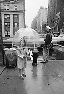 June 1971, New York City, New York State, USA. Transparent umbrellas are becoming the hottest fashion accessory in New York. Their practical transparent surround and mushroom shape without the classic protruding spikes makes them less dangerous than their predecessors. They are also a great boon for glasses wearers and women's hairstyles, especially on windy days.