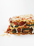 A square of vegetable lasagne with mozzarella cheese, zucchini, onion, red pepper, and tomato sauce