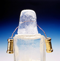 WEIGHTED WIRE CUTS THROUGH BLOCK OF ICE (3 of 4)<br /> Regelation of Ice<br /> The pressure exerted on the ice by the weighted wire lowers the melting point of ice causing it to liquefy under the wire.  As the wire passes thru, the ice refreezes behind it.  Wire is 1/2 thru the ice.