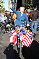 NEW YORK, NY - NOVEMBER 7: A unidentified woman in a Hillary Clinton costumes gives a thumbs up as she rides a bicycle decorated with American flags past Trump Tower  on the day before the U.S. presidential election in New York, New York on November 7, 2016.  Photo Credit: Rainmaker Photo/MediaPunch
