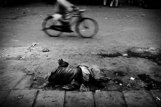 A beggar lays on the street after a political rally by the ethnic Hazara presidential candidate, Ramazan Bashardost, in a market in Kabul, Afghanistan, on August 14, 2009. Presidential and provincial council elections took place on August 20 amidst insecurity and Taliban intimidation. After allegations of fraud, a run off election was scheduled for November 7 between favorites Hamid Karzai and Dr. Abdullah Abdullah, however Dr. Abdullah withdrew before the second round and Karzai was named president for second term. Photo by Adam Ferguson/VII Mentor Program