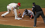 Cardinals firstbaseman Matt Adams reaches as he tries to tag out Boston's Shane Victorino, who dives back to first to avoid the pickoff.  At right is first base umpire Paul Emmel.