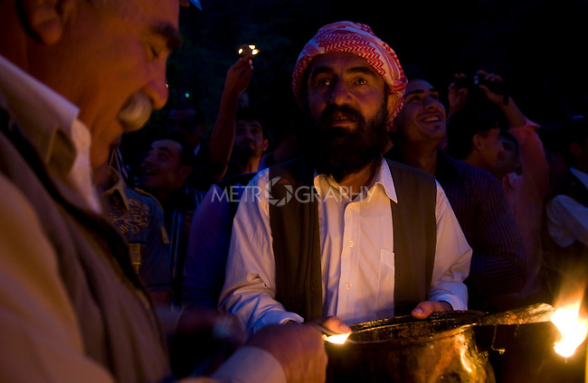 LALISH VALLEY, IRAQ: A Yezidi religious leader hands out  candle wicks dipped in oil for the crowd to burn...The Yezidis, a minority religious group found in northern Iraq, celebrate Chwar Shema Sur (Red Thursday), as part of their New Year festival.  The Yezidis are the religious descendants of Zoroastrians and as a religious minority in Iraq are often targeted by terrorists.