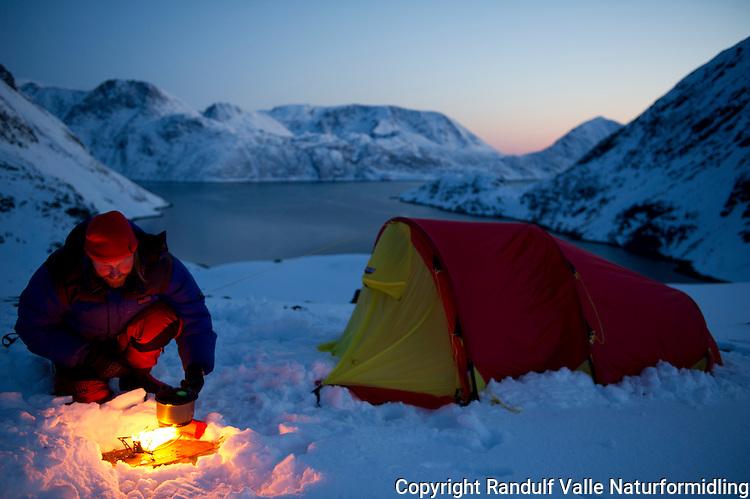 Mann fyrer primus utenfor telt på østsiden av Jøfjorden på Seiland. ---- Man priming stove outside tent on the east side of Jøfjorden on Seiland.