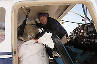 February 16, 2013  Volunteer Iditarod Air Force pilot, Jay Holtan, loads his plane at the Willow airport as musher food, straw, HEET and people food is flown to the 4 checkpoints on the east side the Alaska Range. ..Iditarod 2013   Photo Copyright Jeff Schultz  -- Do not reproduce without written permission