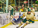 4 January 2014:  University of Vermont Catamount Forward Connor Brickley, a Senior from Everett, MA, charges Yale University Bulldog defenseman Ryan Obuchowski, a Sophomore from West Bloomfield, MI, and shatters the arena glass with a skate, delaying the game in the second period at Gutterson Fieldhouse in Burlington, Vermont. With an empty net and seconds remaining, the Cats came back to tie the game 3-3 against the 10th seeded Bulldogs. Mandatory Credit: Ed Wolfstein Photo *** RAW (NEF) Image File Available ***