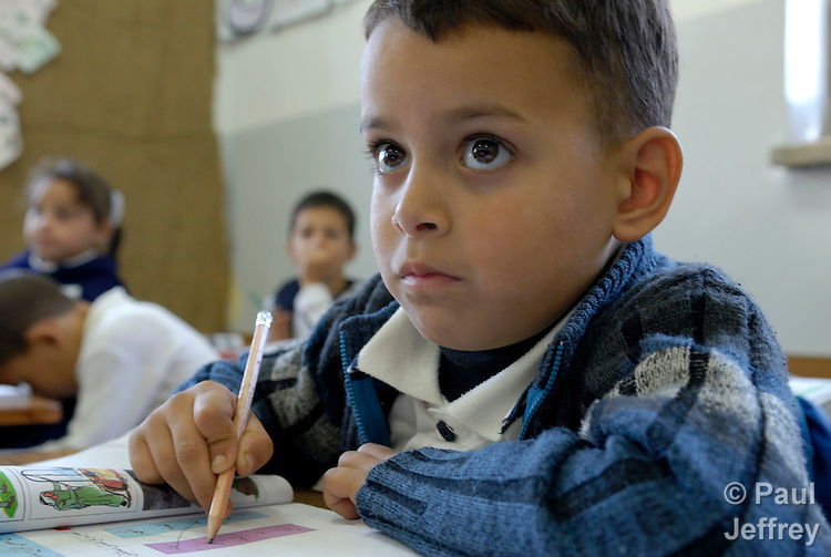 A boy in class at a school run by the Catholic church in the West Bank village of Aboud. Muslim and Christian students live and study together in peace..
