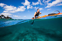 A man paddling an outrigger canoe off the coast of O'ahu.