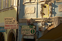 Czeck Republic - Prague, Signs on busy Mosteká in Malá Strana advertise travelers services.
