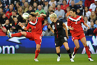 Canada defender Carmelina Moscato (4) clears the ball watched by Megan Rapinoe (15) USWNT and Emily Zurrer (2).