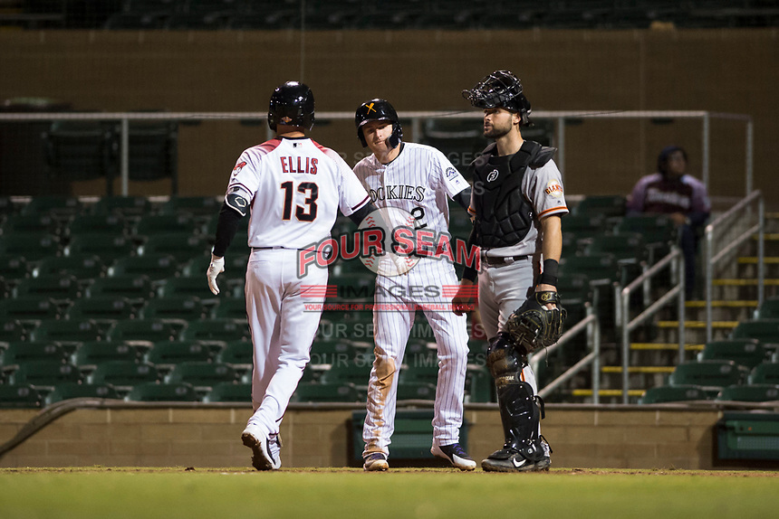 Salt River Rafters first baseman Tyler Nevin (2), of the Colorado Rockies organization, congratulates Drew Ellis (13) after he hit a home run as catcher Matt Winn (16) looks on during an Arizona Fall League game against the Scottsdale Scorpions at Salt River Fields at Talking Stick on October 11, 2018 in Scottsdale, Arizona. Salt River defeated Scottsdale 7-6. (Zachary Lucy/Four Seam Images)