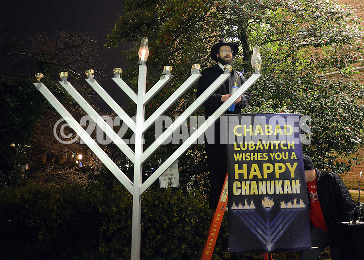 """DOYLESTOWN, PA - DECEMBER 16: Rabbi Mendel Prus of the Lubavitch of Doylestown lights a menorah during a Hanukkah  celebration at the Bucks County Courthouse December 16, 2014 in Doylestown, Pennsylvania. After the lighting of the menorah, the group continued the celebration of the """"festival of lights"""" inside the courthouse. (Photo by William Thomas Cain/Cain Images)"""