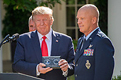 "United States President Donald J. Trump, left, holds a moment presented by General John W. ""Jay"" Raymond, Commander, Air Force Space Command, right, during a ceremony announcing the establishment of the US Space Command in the Rose Garden of the White House in Washington, DC on Thursday, August 29, 2019.  The Space Command will be the lead military agency for the planning and execution of space operations and will be a step towards establishing a Space Force as a new military service.<br /> Credit: Ron Sachs / Pool via CNP"