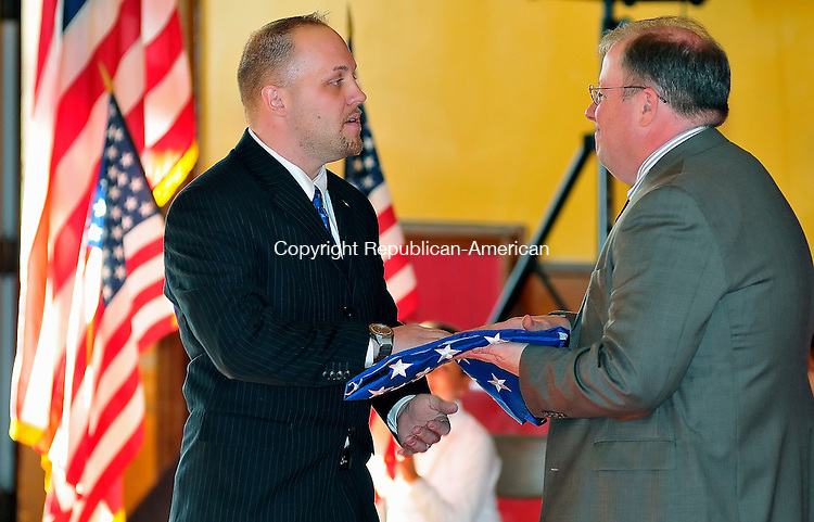 NAUGATUCK, CT-07 JANUARY 2009-010710JS02-Former United States Marine Sgt. Kevin Braziel presents an American flag to St. Francis School principal Thomas Fuller, right, during a ceremony Thursday at the school in Naugatuck. The flag flew over the United State embassy in Afghanistan. The flag was given as a token of gratuitude for donations the students collected for soldiers serving in Afghanistan.<br /> Jim Shannon Republican-American