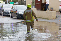 Pictured: A fireman wades through a flooded road off Dulais Fach Road (B4434) between the areas of Aberdulais and Tonna in Neath, south Wales, UK. Saturday 13 October 2018<br /> Re: Flooding caused by Storm Callum in the Neath area, south Wales, UK.