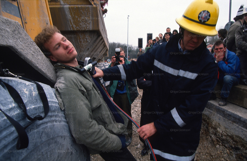 Fireman uses hydraulic cutter to release Jason Torrance who is attached with U-lock to plant machinery in the Cutting. Road Protest actions at Twyford Down, near the Donga pathways, outside Winchester, against the M3 road extension. 1992-94<br />